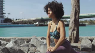 Young fit black woman with short curl wearing sportive clothing and training on rocky embankment of city river.