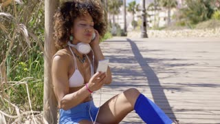 Young fit female in swimsuit and shorts sitting on ground and listening to music with headphones.