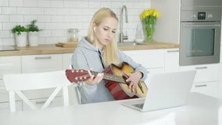 Young girl practicing guitar while sitting at home in light modern kitchen and using laptop with headphones.