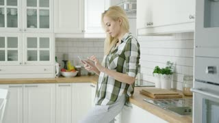 Young girl wearing home clothing and standing in light and modern kitchen while using smart phone.