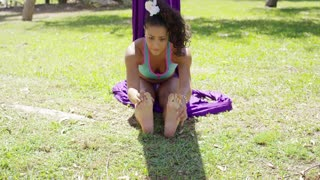 Young gymnast working out in a park doing the splits stretching her muscles to improve flexibility and mobility