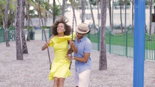 Young handsome man helping to cheerful laughing ethnic woman to swing on the playground in the park.