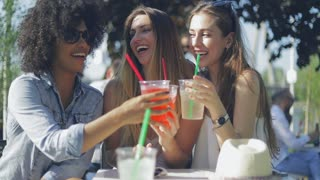 Young happy women wearing summer outfits clinking glasses with drinks while sitting at table in outside cafe and enjoying time together