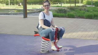 Young laughing female in eyeglasses riding spring toy on playground and looking at camera.
