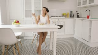 Young lovely girl wearing home clothing sitting at table in modern light kitchen and eating alone.