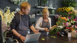Young man in striped apron using laptop while woman standing near at counter and taking care of flowers arranging bouquet.