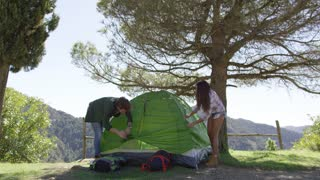 Young people putting up tent at place of rest under trees while hiking in mountains in summer.