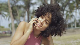 Young pretty African-American sitting on lawn in summer park enjoying sunlight with eyes clsoed and talking on smartphone.