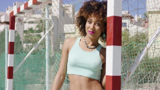 Young pretty girl wearing summer outfit standing near football gates and posing while smiling at camera.