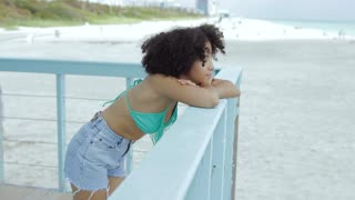 Young relaxed black girl in swimsuit and short leaning on fence of lifeguard tower and looking away observing nature.