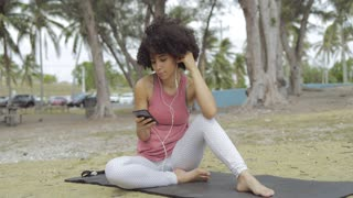 Young relaxing black girl in sportswear listening to music with headphones sitting on mat in tropical park.