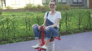 Young smiling female in eyeglasses riding spring toy on playground and looking at camera.