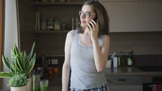 Young smiling female in eyeglasses talking on smartphone standing in kitchen and looking away.