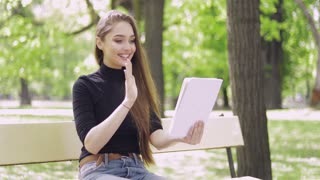 Young smiling woman in casual outfit sitting on bench in park and using tablet for online conversation