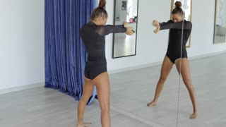 Young sportive black attractive woman standing and dancing alone in dance class.