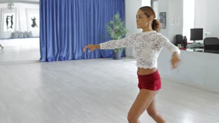 Young sportive woman dancing gracefully with great concentration looking content on background of modern light dancing studio.