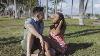 Young stylish black woman with cheerful man sitting on lawn in park and chatting with laugh having fun in sunlight.