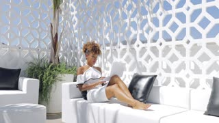 Young trendy woman in elegant white dress watching laptop while chilling on white sofa on resort hotel terrace.