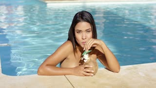 Young woman drinking tropical coconut cocktails in the pool as she leans against the tiled surround in her swimsuit enjoying her summer vacation
