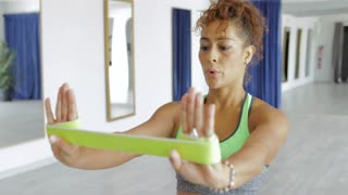 Young woman in sportswear training hands with special elastic band looking concentrated on background of modern light studio.