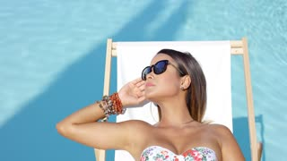Young woman in sunglasses relaxing in the summer sun as she reclines on a comfortable deck chair at the edge of the swimming pool