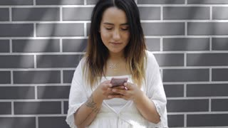 Young woman reading a text message on her cellphone or smartphone standing in front of a dark grey brick wall with copy space