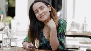 Young woman sitting alone in outdoor restaurant and looking at camera with friendly smile