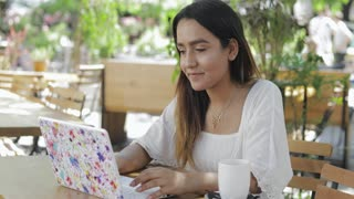 Young woman sitting working on a laptop computer at an outdoor cafeteria under shady trees with a look of concentration