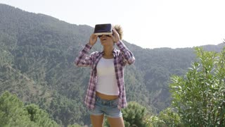 Young woman standing on top of mountain in VR headset and looking around on background of mountains.