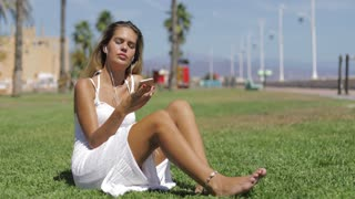 Young wonderful girl posing in white dress sitting barefoot on green meadow enjoying music with smartphone and headphones in bright tropical sunlight.