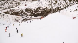 View from a ski lift of skiers below on a run