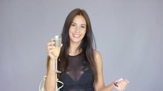 Vivacious attractive stylish young woman having fun at a New Year party cheering and raising a toast with a glass of champagne amidst falling confetti