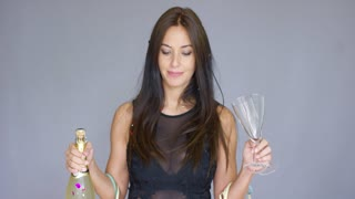 Vivacious woman partying at New Year holding a glass and bottle of champagne in her hands as she stands under a shower of confetti grinning at the camera.