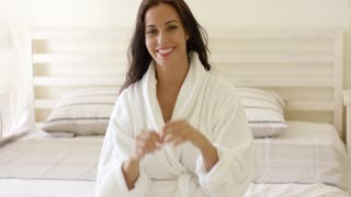 Vivacious young woman with a lovely smile sitting on her bed in a clean white bath robe running her hands through her long hair