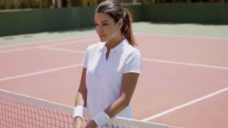 Waist Up Portrait of Smiling Attractive Young Brunette Woman Wearing White Tennis Outfit and Holding Racket on Sunny Outdoor Court