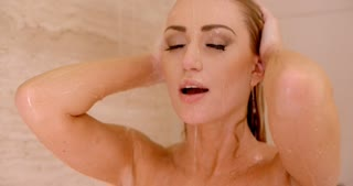 Wet Woman Under a Shower with Hands on Head