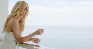 Woman Enjoying View of Ocean from Balcony