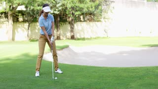 Woman golfer about to play a stroke on the green lining up her ball with the flag in the hole in an active lifestyle concept