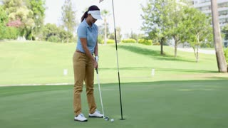 Woman golfer about to sink her putt lining up her ball with the hole on the green on a sunny golf course