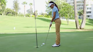 Woman golfer lining up for a putt on the green viewed from the point of view of the flag in the hole