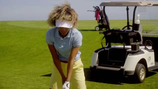 Woman golfer preparing to play a stroke