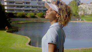 Woman golfer walking beside a lake
