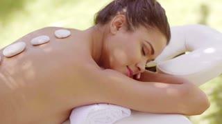 Woman having a hot stone spa massage