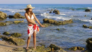 Woman hula dancing on seaweed covered surf while wearing wrap skirt with flower design and a straw hat