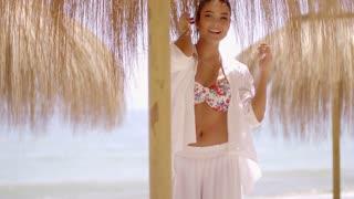 Woman in bikini and under umbrella at beach