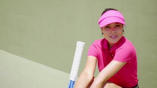 Woman in bright pink shirt and visor while seated near tennis court wall as sun shines overhead