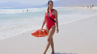 Woman in bright red lifeguard outfit whistle floatation device and calm expression on beach with swimmers