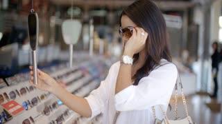 Woman In Optical Store Choosing Eyeglasses