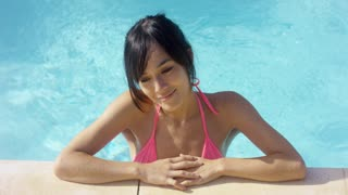 Woman in pink swim suit smiles to herself while standing in an empty pool