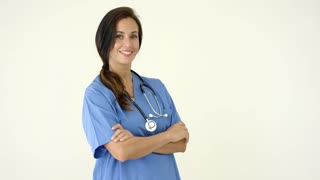 Woman in scrubs crosses arms and smiles at camera with stethoscope around her neck